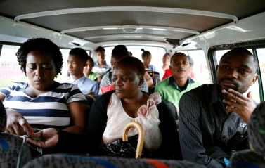 Passengers pass their fares to minibus taxi driver Zakes Hadebe as they commute from Soweto township to central Johannesburg